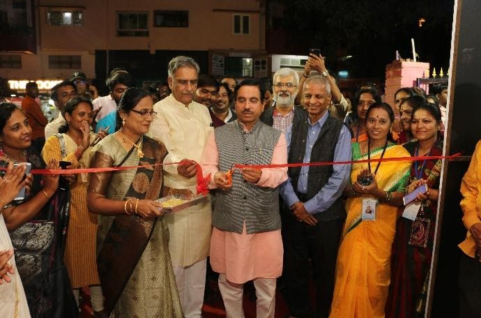 Indian man in pink long sleeves and gray vest cuts red ribbon in event with group of people around